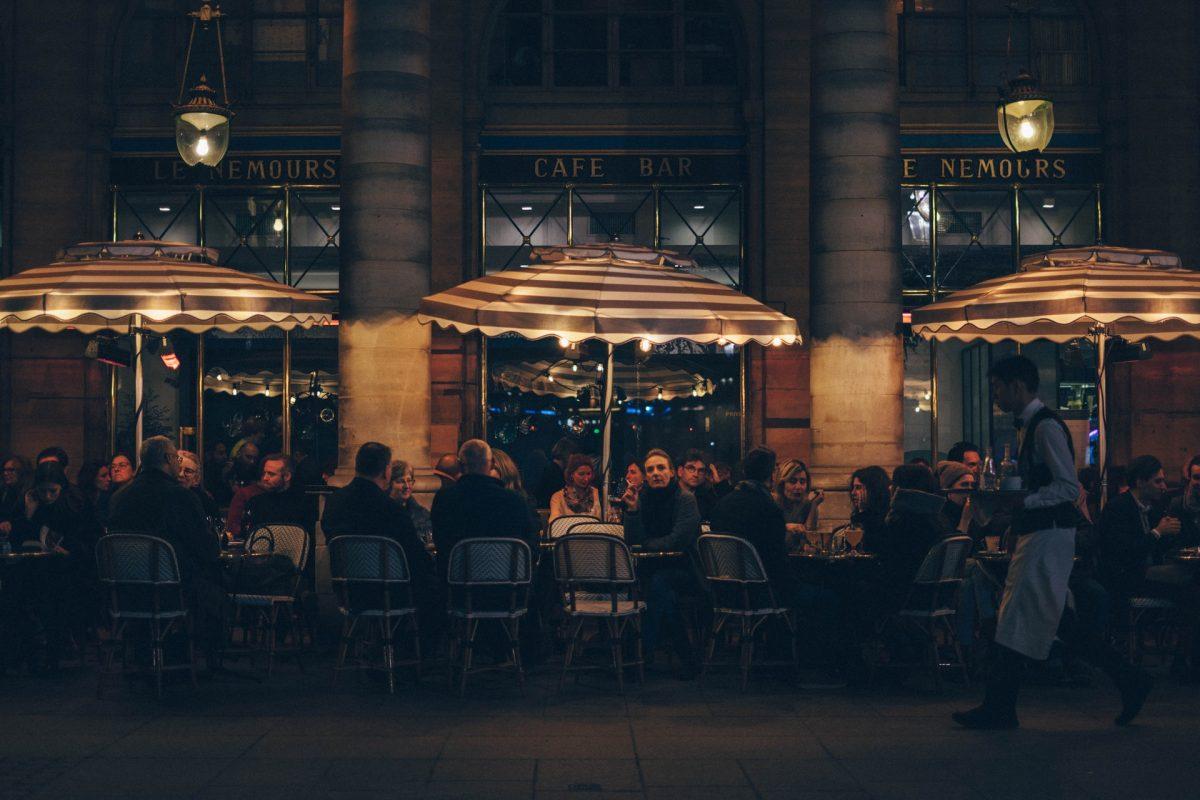 bistro francese di sera con tavolini e persone che mangiano
