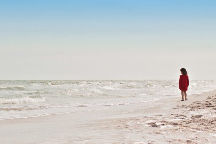 bambina in spiaggia davanti alle onde del mare